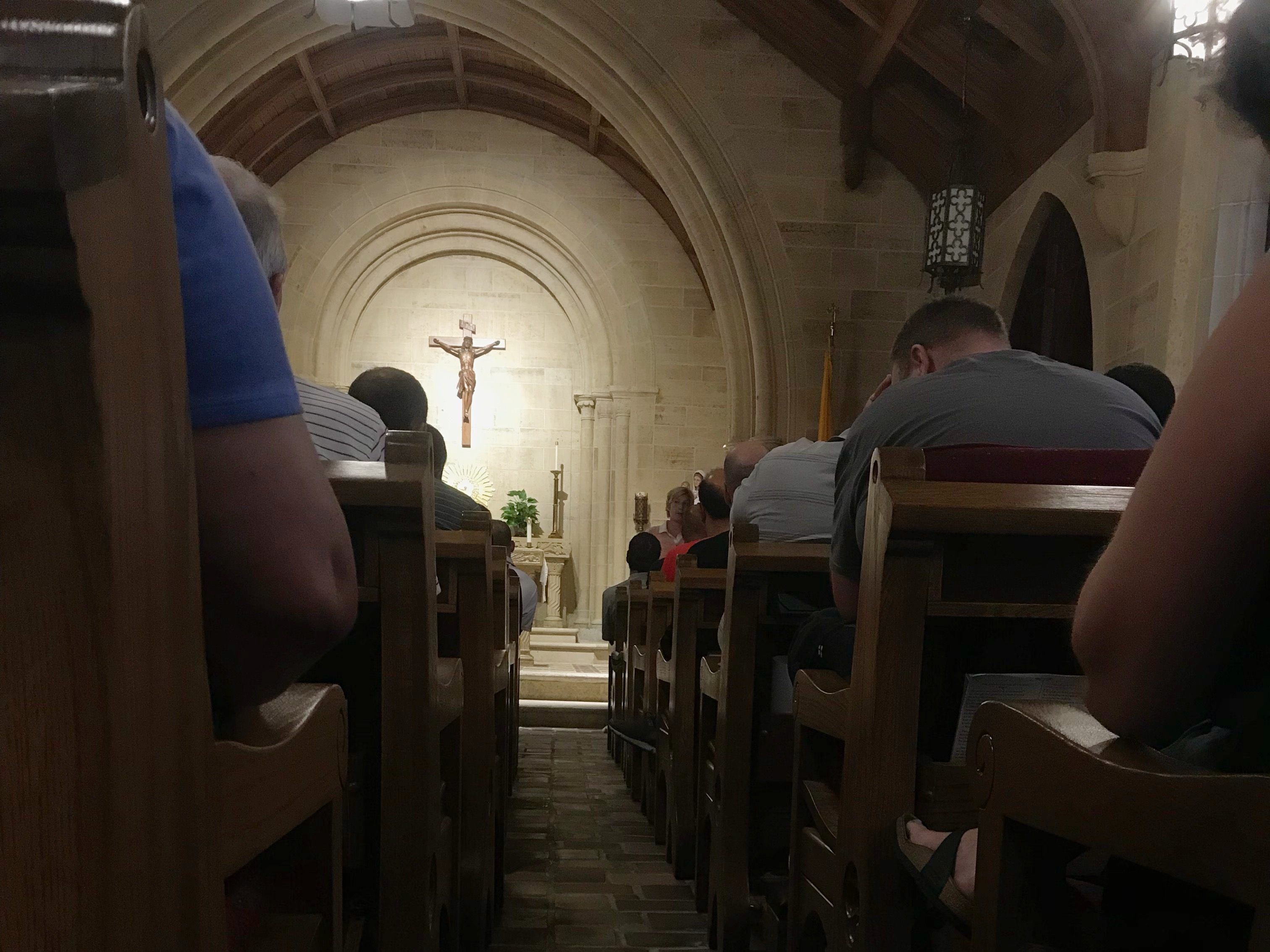 teachers in pews at Mass with light shining on cross