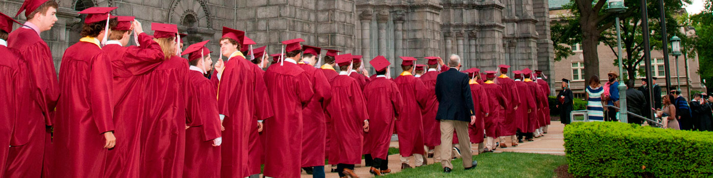 line of graduates in maroon robes in front of cathedral